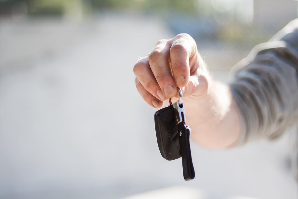 Hand Holding Car Keys Reaching Out