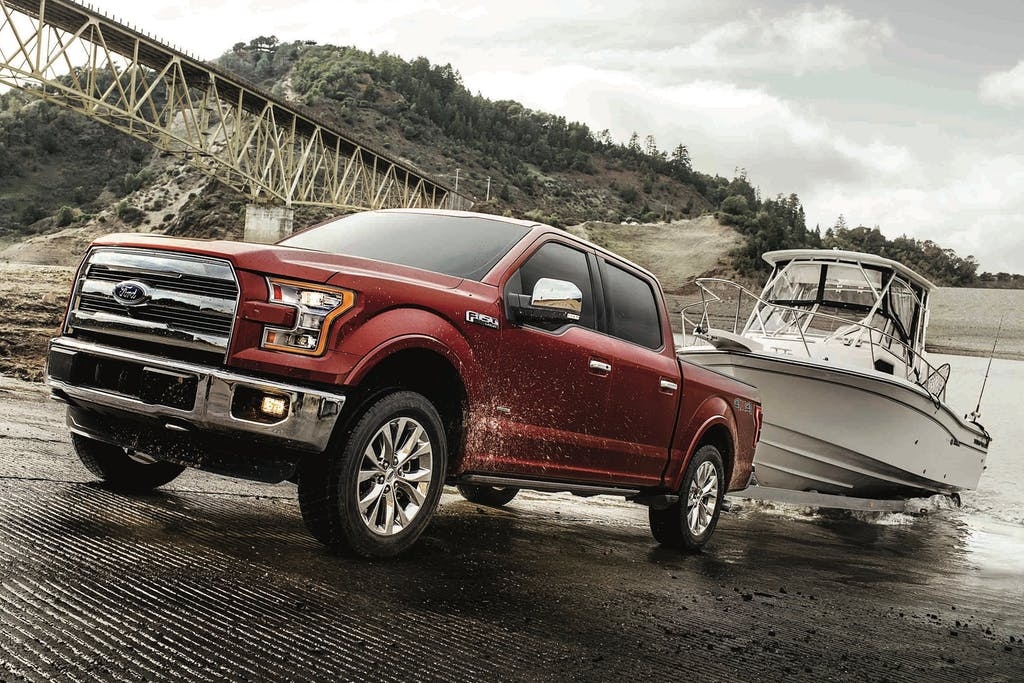 Red Ford F-150 Lariat towing a Boat