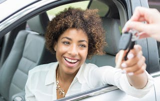 An excited young woman smiles as she reaches from the driver's seat of her new car for her car keys. Only the hand of her car dealer can be seen giving her the keys.