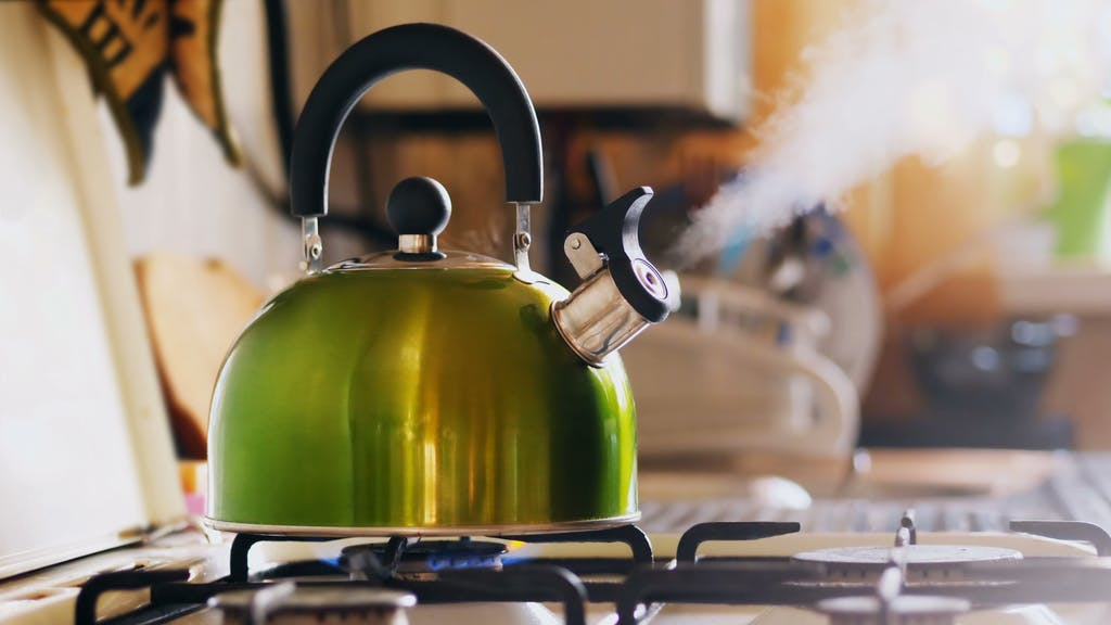 Kettle boiling on a gas stove. Boiling green kettle boiling with steam emitted from spout. Shallow depth of field. Solar glare from the kitchen window