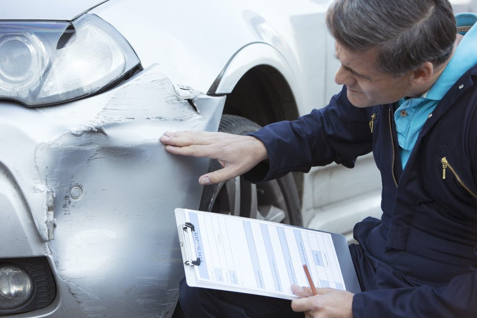 Auto Workshop Mechanic Inspecting Damage To Car