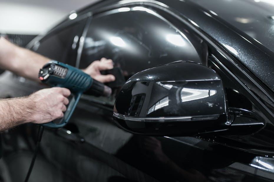 Car window tinting; worker applies tinting foil on car window.