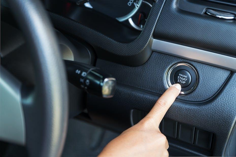 closeup hand pushing on car start button