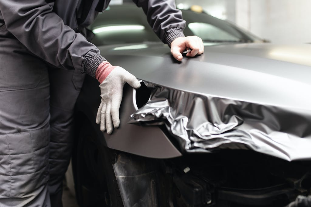 Car wrap specialist putting vinyl foil or film on car. Selective focus.