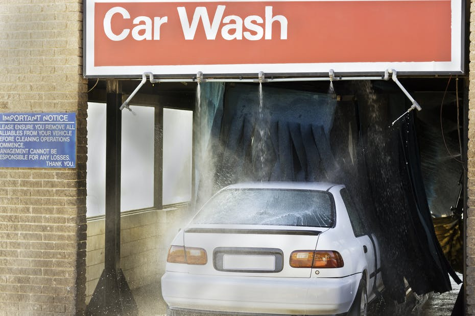 Vehicle seen being washed with an industrial car washing machine, at a garage or gas station car wash