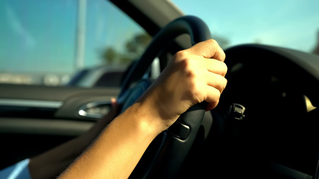 Persons Hands on a Steering Wheel
