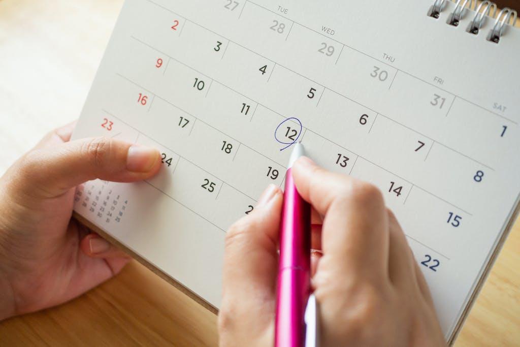 a hand circling a date on a calendar